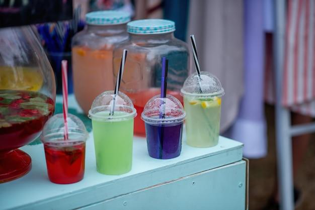 Em um festival de comida de rua, coquetéis coloridos são expostos no balcão em copos descartáveis com canudos, soltando fumaça de gelo artificial em seu interior. sangria de vinho, limonadas caseiras.