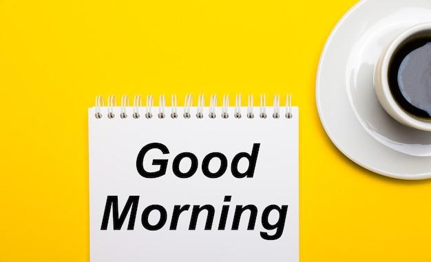 Em um fundo amarelo brilhante, uma xícara branca com café e um bloco de notas branco com as palavras bom dia