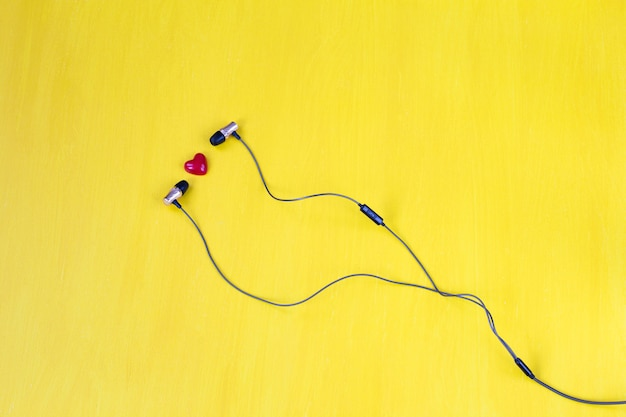 Em um fundo amarelo fones de ouvido e um coração vermelho