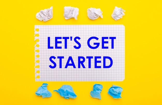 Em um fundo amarelo, pedaços de papel amassados em branco e azul e um caderno com o texto começando.