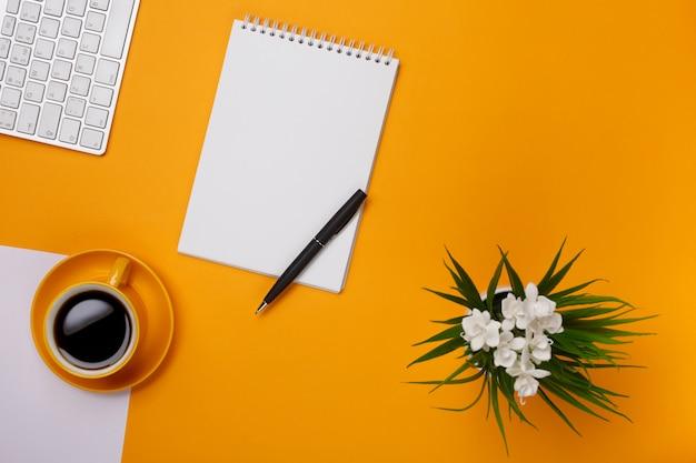 Em um fundo amarelo uma caneta com um teclado e uma xícara de café preto