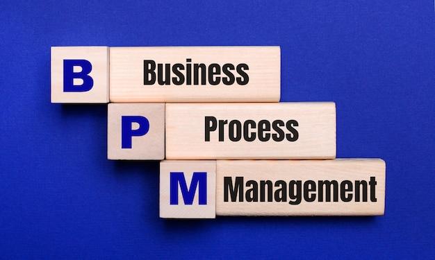 Em um fundo azul brilhante, cubos e blocos de madeira claros com o texto bpm business process management