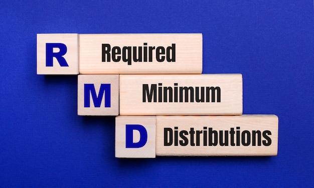 Em um fundo azul brilhante, cubos e blocos de madeira claros com o texto distribuições mínimas exigidas de rmd