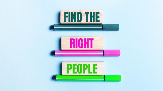 Em um fundo azul claro, há três canetas de feltro multicoloridas e blocos de madeira com o botão encontrar as pessoas certas