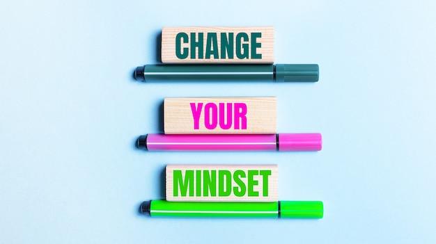 Em um fundo azul claro, há três canetas de feltro multicoloridas e blocos de madeira com o botão mude sua mentalidade
