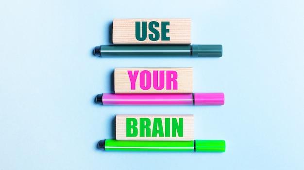 Em um fundo azul claro, há três canetas hidrográficas multicoloridas e blocos de madeira com o botão use sua marca
