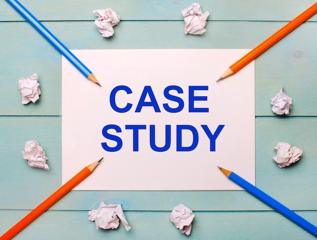Em um fundo azul - lápis preto e laranja, folhas de papel branco amassadas e uma folha de papel branca com o texto estudo de caso