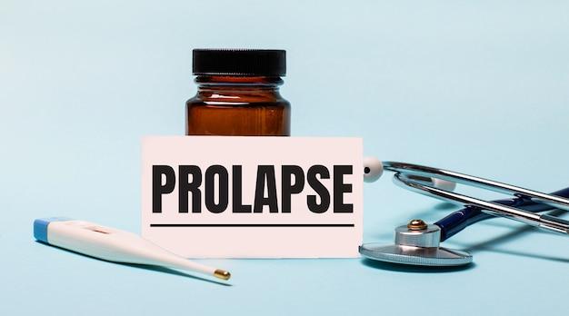 Em um fundo azul - um frasco de comprimidos, um estetoscópio, um termômetro eletrônico e um cartão com a inscrição prolapse