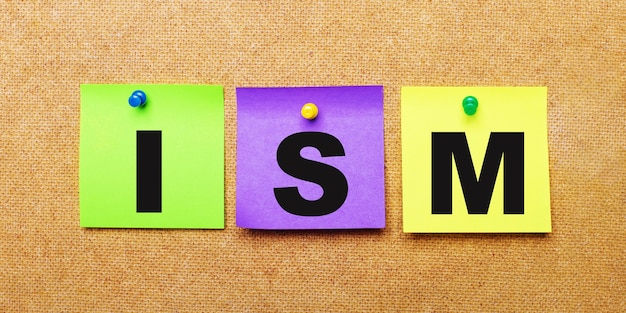 Em um fundo bege, adesivos multicoloridos para anotações com a palavra ism