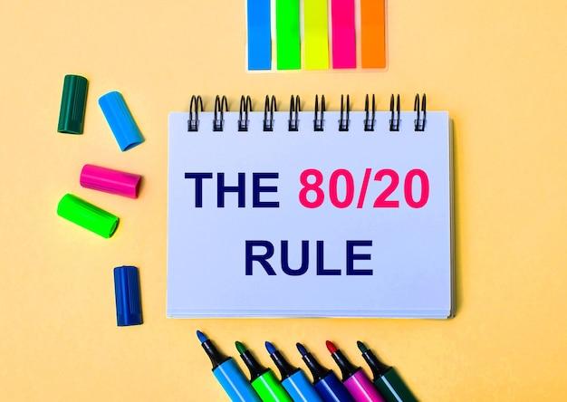 Em um fundo bege, um caderno com as palavras the 80 20 rule, canetas hidrográficas brilhantes e adesivos