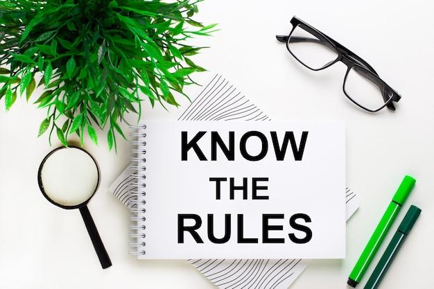 Em um fundo branco está um caderno com a palavra conheça as regras, óculos, uma lupa, marcadores verdes e uma planta verde