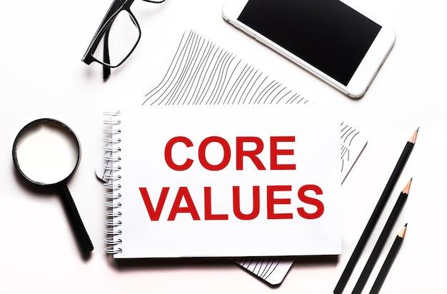 Em um fundo branco óculos, uma lupa, lápis, um smartphone e um caderno com o texto core values