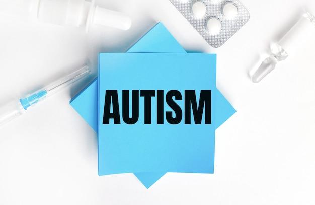 Em um fundo branco, uma seringa, ampola, pílulas, um frasco de remédio e adesivos azuis claros com a inscrição autismo