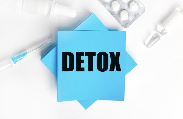 Em um fundo branco, uma seringa, ampola, pílulas, um frasco de remédio e adesivos azuis claros com a inscrição detox.