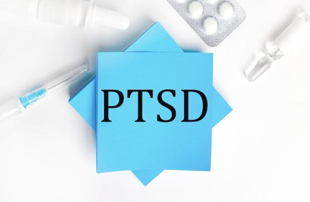 Em um fundo branco, uma seringa, ampola, pílulas, um frasco de remédio e adesivos azuis claros com a inscrição ptsd. conceito médico