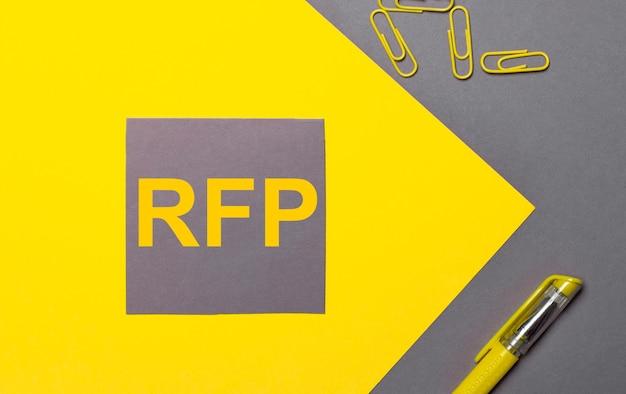 Em um fundo cinza e amarelo, um adesivo cinza com texto amarelo rfp, clipes de papel amarelos e uma caneta amarela