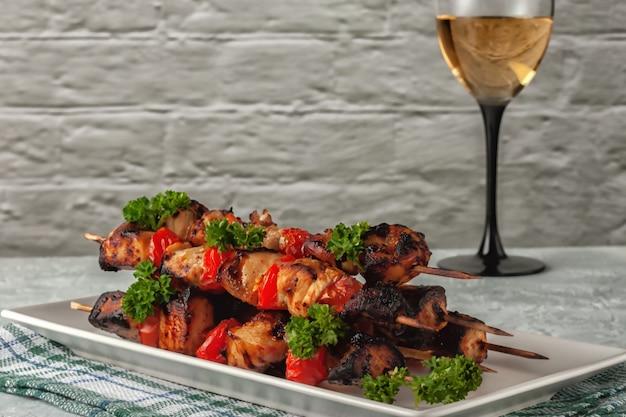 Em um fundo cinza espetos de frango com legumes e uma taça de vinho branco
