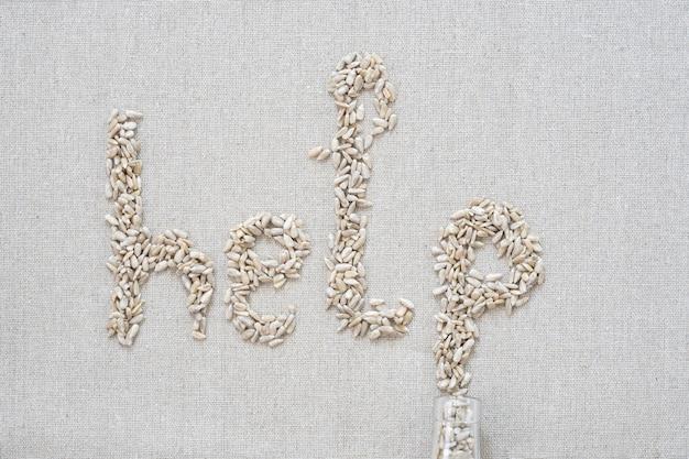 Em um fundo cinza, há sementes em forma de letras e a palavra