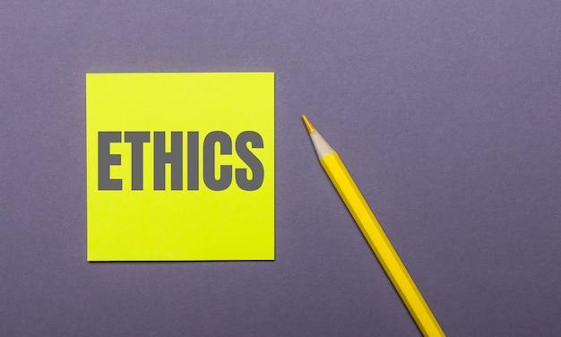 Em um fundo cinza, um lápis amarelo brilhante e um adesivo amarelo com a palavra ética
