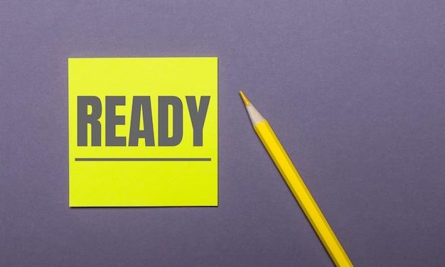 Em um fundo cinza, um lápis amarelo brilhante e um adesivo amarelo com a palavra pronto
