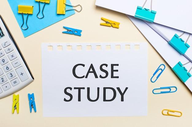 Em um fundo claro, há pilhas de documentos, uma calculadora branca, clipes e prendedores de roupa amarelos e azuis e um caderno com o texto estudo de caso