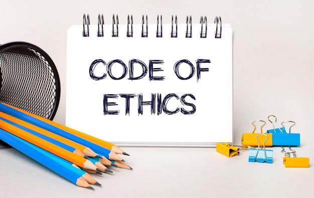 Em um fundo claro, lápis amarelos e azuis e clipes de papel e um caderno branco com o texto código de ética