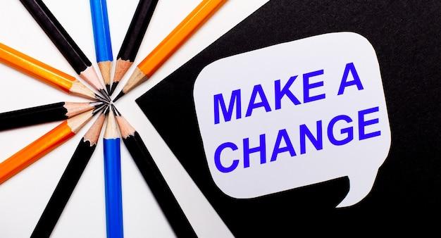 Em um fundo claro, lápis multicoloridos e em um fundo preto um cartão branco com o texto faça uma mudança