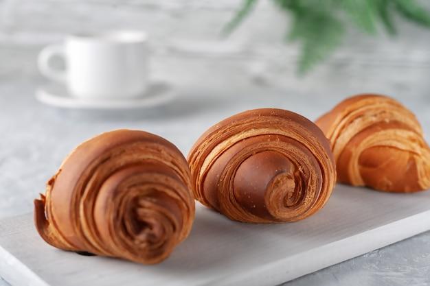 Em um fundo claro, um croissant perfumado recém-assado com uma xícara de leite