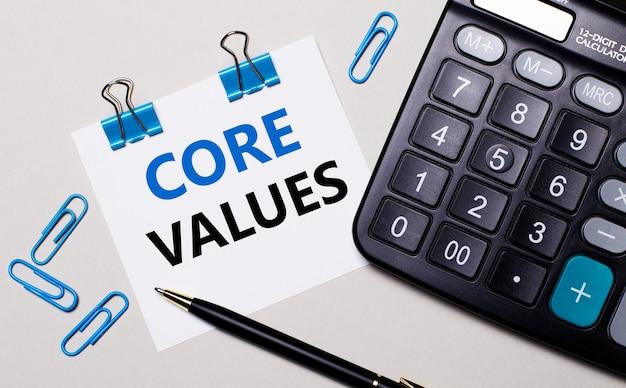 Em um fundo claro, uma calculadora, uma caneta, clipes de papel azuis e uma folha de papel com o texto core values