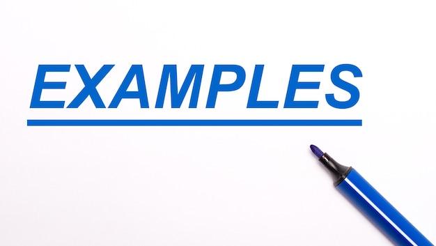 Em um fundo claro, uma caneta hidrográfica azul aberta e o texto exemplos
