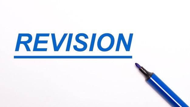 Em um fundo claro, uma caneta hidrográfica azul aberta e o texto revisão