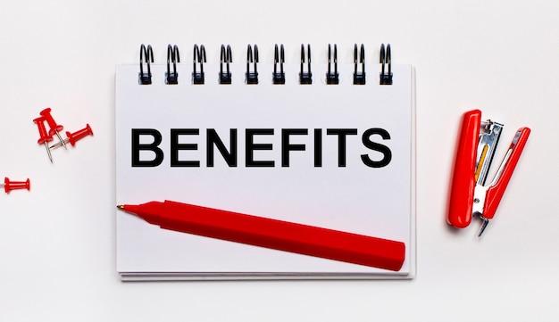 Em um fundo claro, uma caneta vermelha, um grampeador vermelho, clipes de papel vermelhos e um caderno com a inscrição benefícios