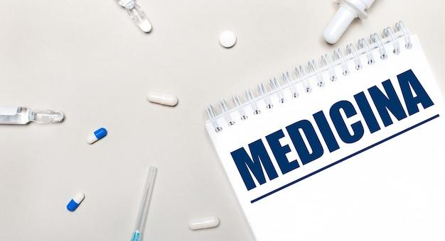 Em um fundo claro, uma seringa, um estetoscópio, frascos de remédio, uma ampola e um bloco de notas branco com o texto medicina