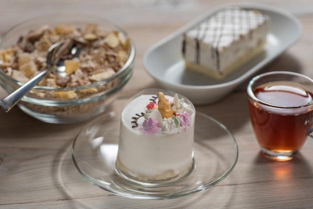 Em um fundo de madeira chocolate, bolo infantil, uma xícara de chá e muesli com frutas secas
