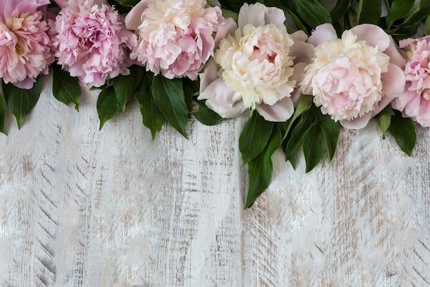 Em um fundo de madeira clara rosa peônias