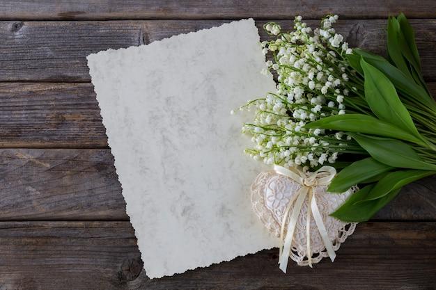 Em um fundo de madeira lírios do vale, um pedaço de papel e um coração feito de renda