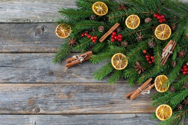 Em um fundo de madeira ramos de abeto, canela, anis, rodelas de limão, frutas vermelhas