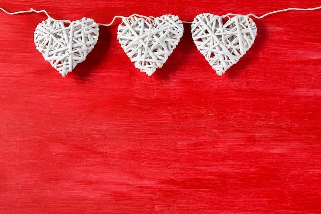 Em um fundo de madeira vermelho três corações brancos. espaço livre para texto.