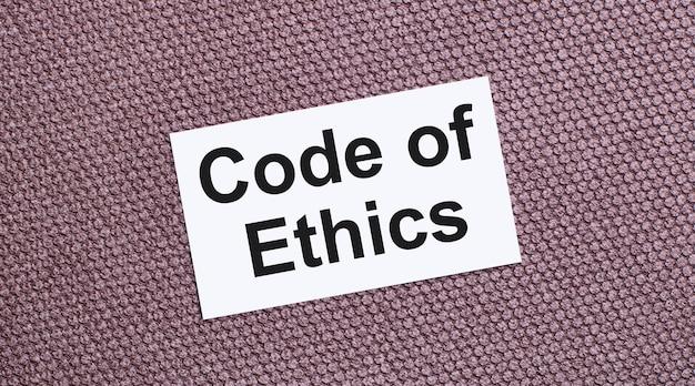 Em um fundo marrom, um cartão retangular branco com o texto código de ética