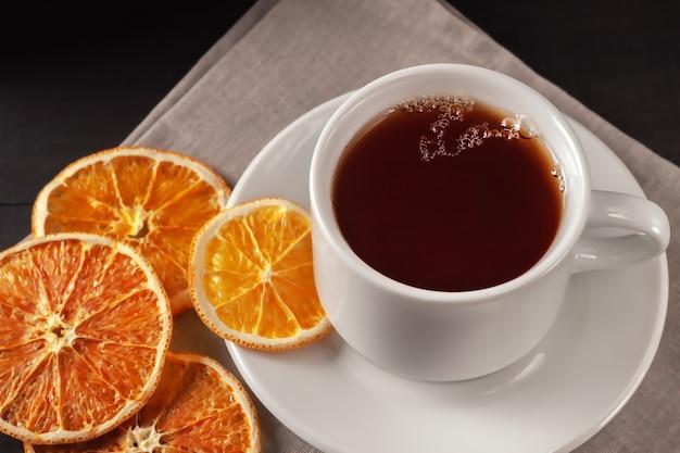 Em um fundo preto de madeira, uma xícara de chá com rodelas de laranja secas