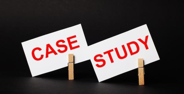 Em um fundo preto em prendedores de roupa de madeira, dois cartões brancos em branco com o texto estudo de caso