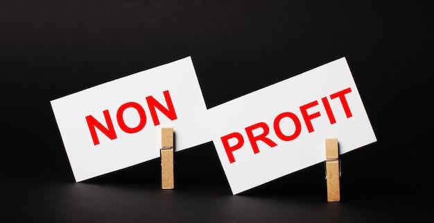 Em um fundo preto em prendedores de roupa de madeira, dois cartões brancos em branco com o texto sem lucro
