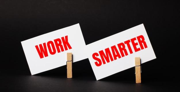 Em um fundo preto em prendedores de roupa de madeira, dois cartões brancos em branco com o texto trabalhe mais inteligente
