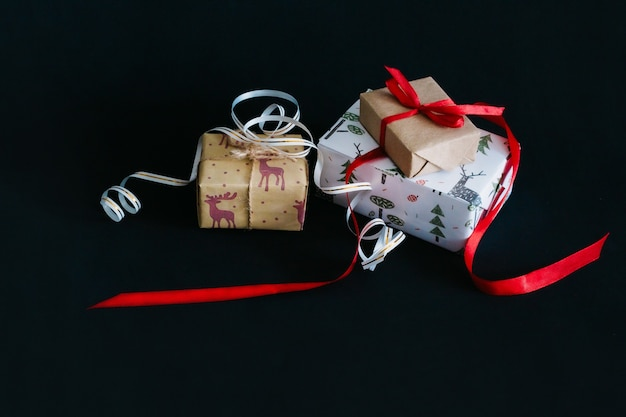 Em um fundo preto estão presentes de natal embrulhados em papel de embrulho e amarrados com fitas, uma pequena caixa de artesanato amarrada com uma fita vermelha, uma grande caixa amarrada com uma fita branca com ouro