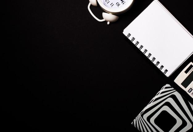 Em um fundo preto, uma calculadora branca, despertador e blocos de notas em branco. copie o espaço