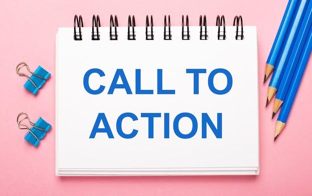 Em um fundo rosa claro, lápis azul claro, clipes de papel e um caderno branco com o texto chamada à ação