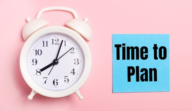 Em um fundo rosa claro, um despertador branco e uma folha de papel azul com o texto hora de planejar