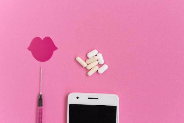 Em um fundo rosa está um smartphone branco, uma seringa, comprimidos e um desenho de lábios vermelhos