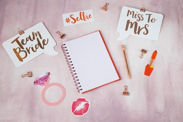 Em um fundo rosa itens para o planejamento de uma festa de despedida: adesivos, caderno, caneta