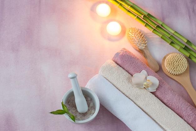 Em um fundo rosa itens para o spa: toalhas, velas, escovas, sal marinho, bambu